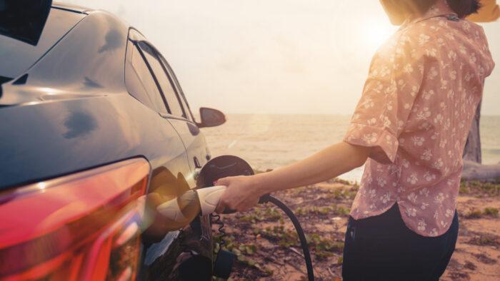 Person med solhatt som laddar elbil i solnedgång