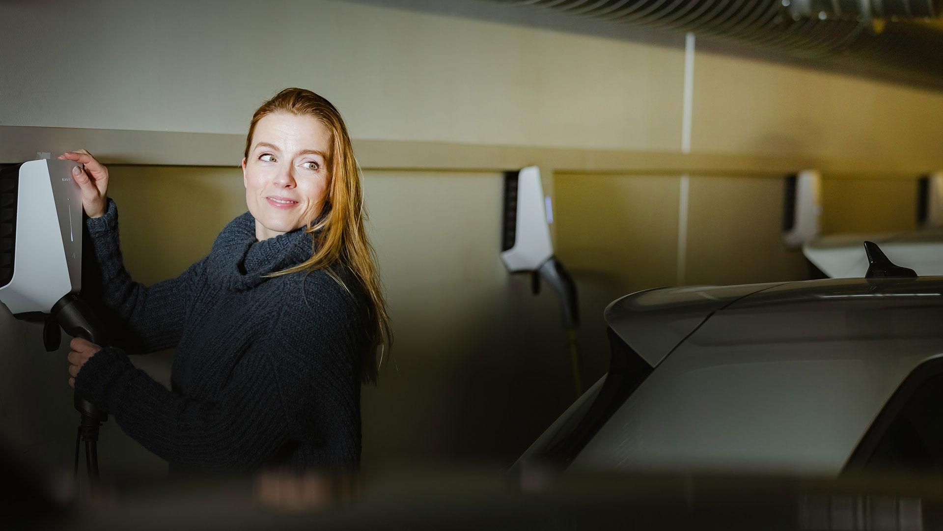 Person som laddar elbil i väggmonterad laddbox